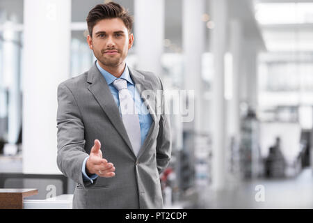 Businessman reaching out his hand - Stock Photo