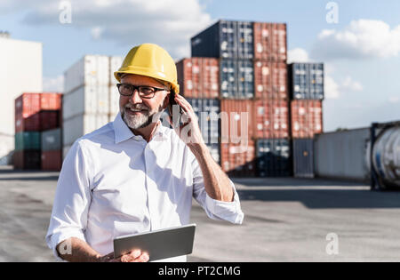 Businessman at cargo harbour, wearing safety helmet, using smartphone and digital tablet - Stock Photo