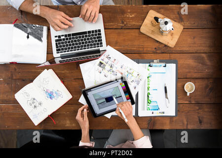 Mature couple working from their home office, using laptop and digital tablet - Stock Photo