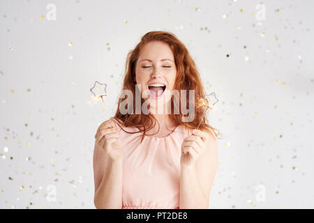Portrait of shouting young woman with two sparklers - Stock Photo