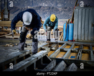 Construction workers working on plywood - Stock Photo