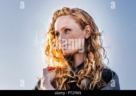 Portrait of redheaded woman outdoors - Stock Photo