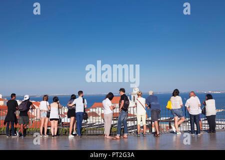 Tourists enjoying the view from the Miradouro de Santa Luzia to theTagus, Lisbon, Portugal - Stock Photo