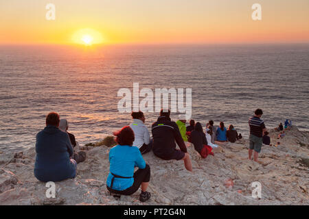 Tourists enjoying sunset at the lighthouse at Cabo de Sao Vicente, Sagres, Algarve, Portugal - Stock Photo