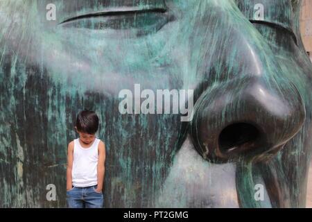 niño  vestido con camiseta blanca posando junto a enorme escultura de rostro en color verde en un día soleado en el centro de Guadalajara - Stock Photo