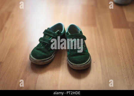 Worn and muddy pair of childs shoes on a wooden floor of a living room. - Stock Photo