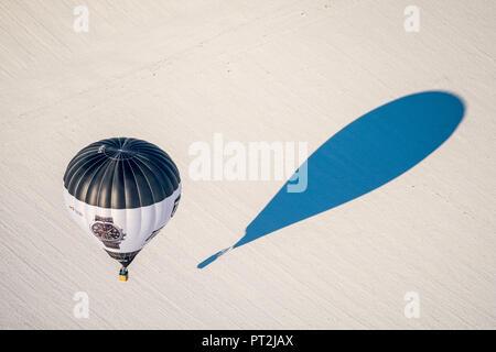 Hot air balloon Tutima D-OTGL during landing on a snow surface, winter weather, Sauerland - Stock Photo