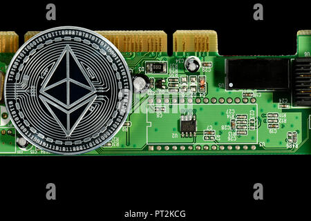 Symbolic image of digital currency, silver physical coin Ethereum on circuit board - Stock Photo