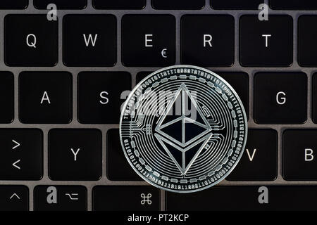 Symbol image of digital currency, silver physical coin Ethereum on keyboard - Stock Photo
