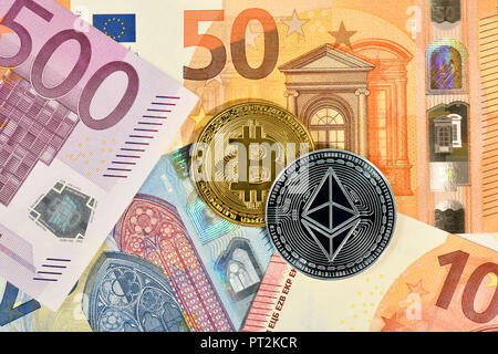 Symbolic image of digital currency, golden physical coin Bitcoin and silver physical coin Ethereum on EURO banknotes - Stock Photo