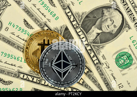 Symbolic image of digital currency, silver physical coin Ethereum and golden physical coin Bitcoin on banknote US dollar - Stock Photo