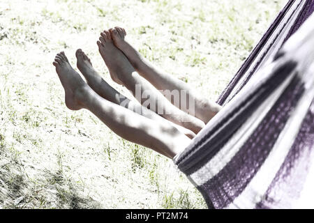 2 girls swing their legs out of a hammock while rocking - Stock Photo