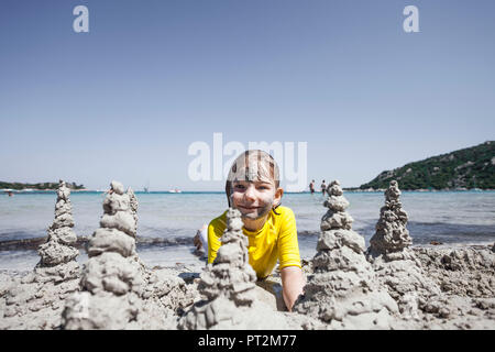 Girl with sand in the face builds sandcastles in beautiful bay - Stock Photo