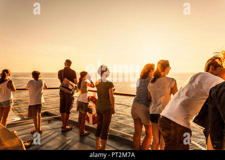 Passengers on a ship look out over the sea into the evening sun - Stock Photo
