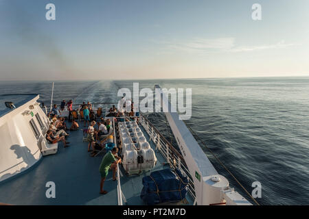 Passengers on deck of a ship overlooking the sea - Stock Photo