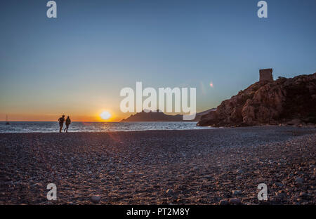 2 people on the beach in front of atmospheric sunset - Stock Photo