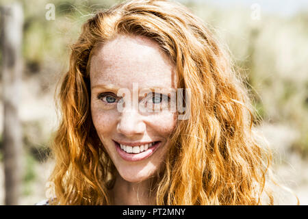 Portrait of smiling redheaded woman - Stock Photo