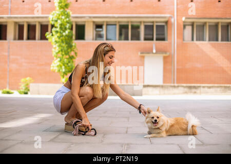 Pretty young woman smiling, caressing a pomeranian - Stock Photo