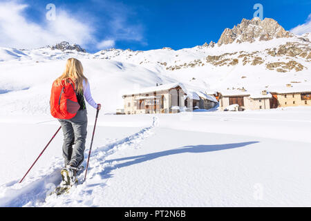 Young girl walks with snowshoes near the village of Grevasalvas, Engadin Valley, Graubünden, Switzerland, Europe, - Stock Photo
