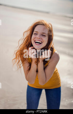 Redheaded woman, laughing happily on the beach - Stock Photo
