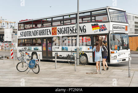 BERLIN, GERMANY - JULY 13, 2018: Tourists visit Berlin Stadtrundfahrten sightseeing bus in front of the central passenger railway station Hauptbahnhof - Stock Photo