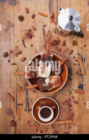 Homemade espresso and white chocolate ice lollies with winter spices, cup of espresso and espresso maker on wooden background - Stock Photo