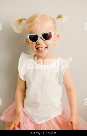 Portrait of blond little girl wearing heart-shaped sunglasses - Stock Photo