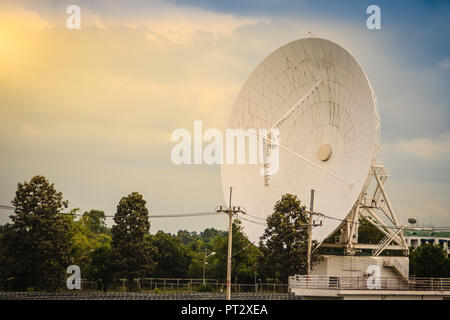 A large scale white satellite dish in solar farm under dramatic blue and cloudy sky background. - Stock Photo