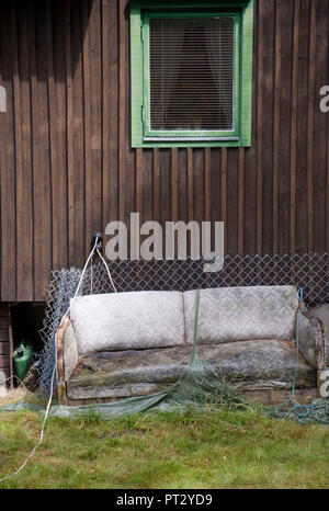 old sofa in front of wooden hut - Stock Photo