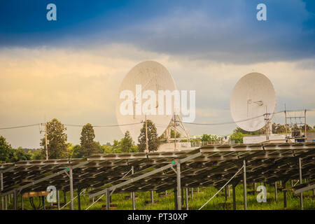 Twin large scale white satellite dish in solar farm under dramatic blue and cloudy sky background. - Stock Photo