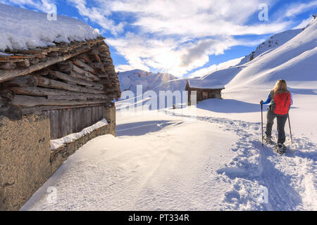Young girl walks with snowshoes between traditional huts, Grevasalvas, Engadin Valley, Graubünden, Switzerland, Europe, - Stock Photo