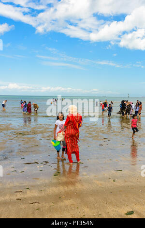 Muslim families enjoying a day out on the beach at Margate, Kent, England, UK - Stock Photo
