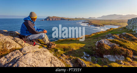 man looking out on the coastline on a clear early morning, location: dingle peninsula in co, kerry, western ireland, Waymont near Graigue, 52, 151437, -10, 475927 - Stock Photo