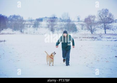 Happy man with a labrador retriever dog running through a snowy field in winter - Stock Photo