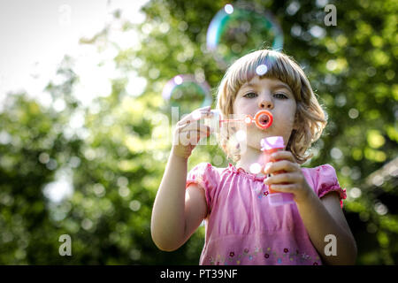 Blonde girl in pink dress blowing soap bubbles - Stock Photo