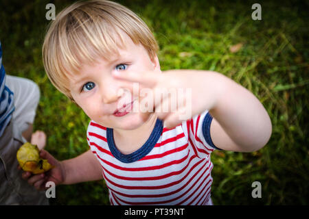 Toddler, two-year-old with red and white striped tee, cheeky, facing camera - Stock Photo
