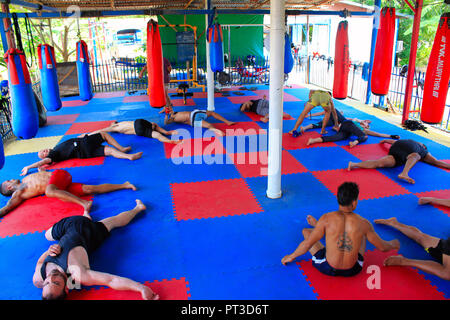 PHETCHABUN, THAILAND, May 2018, People do torso twist stretch a circle before practicing boxing in an open gym at Ban Bung Sam Phan Nok. - Stock Photo