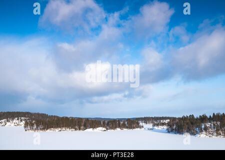 Frozen Saimaa lake under cloudy sky. Rural winter landscape, Finland - Stock Photo