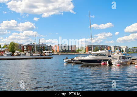 LAPPEENRANTA, FINLAND - JUNE 15, 2016: Pier with yachts and boats on Saima Lake. On the background are residential buildings on Rapasaari Island - Stock Photo