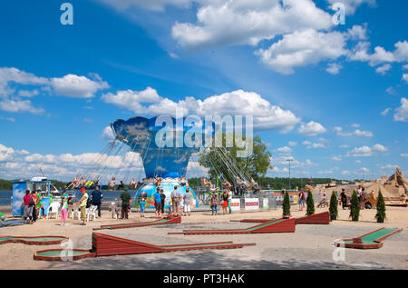 LAPPEENRANTA, FINLAND - JUNE 15, 2016: Adults look at the kids ride the attraction near Saimaa Lake. On the right side is Knight Sandcastle - Stock Photo