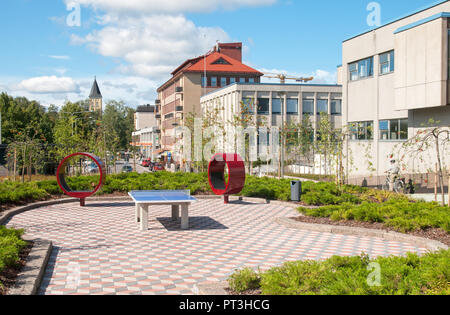LAPPEENRANTA, FINLAND - AUGUST 8, 2016: Tennis table and round red benches near Monari youth community center and City Library - Stock Photo