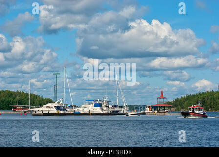 LAPPEENRANTA, FINLAND - AUGUST 8, 2016: Boat floats near pavilion on the small pier with yachts on The Saimaa Lake - Stock Photo