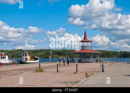 LAPPEENRANTA, FINLAND - AUGUST 8, 2016: Children and adults  near pavilion on the small pier with yachts and boats next to The Saimaa Lake - Stock Photo