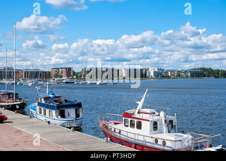 LAPPEENRANTA, FINLAND - AUGUST 8, 2016:  Pier with yachts and boats on Saimaa Lake. On the background are residential buildings on Rapasaari Island - Stock Photo