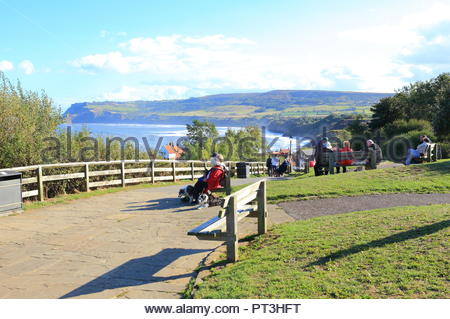 Tourists sitting on benches overlooking the North Sea at Robin Hood's Bay, North Yorkshire UK. September 2018 Autumn, Afternoon - Stock Photo