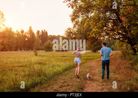 Young couple walking pug dog in autumn forest. Happy puppy running along and having fun playing with master outdoors. - Stock Photo