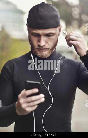 Close-up shot of young white man with beard putting headphone in his ear. Determined sportsman is ready for long-distance run and workout Athlete wear - Stock Photo