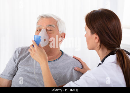 Young Female Doctor Holding Oxygen Mask Over Senior Male Patient's Face - Stock Photo