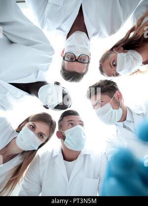 Surgical team working on a bleeding patient in a surgical room - Stock Photo