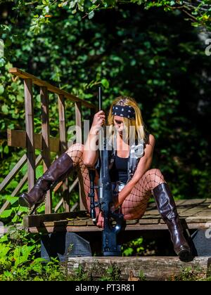 Pretty attractive young woman acting tired female soldier holding rifle in hands between legs - Stock Photo